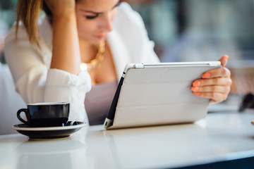 Young businesswoman using tablet computer in coffee shop