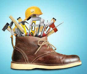 Tools and construction helmet in a big Shoe