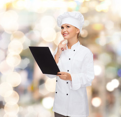 smiling female chef with black blank paper