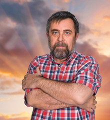 Middle-aged man on cloudy sky background