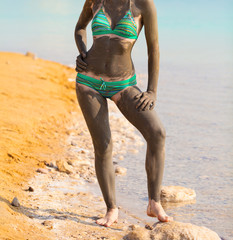 Woman smeared with mud on the beach