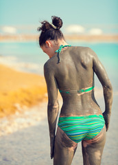 Woman smeared with mud on the beach back to camera
