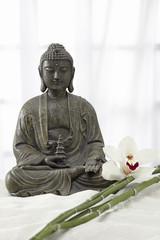 Buddha Statue mit Bambus und Orchideenblüte