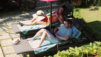 Couple using modern technology on sunbeds