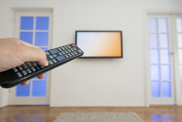 Holding TV remote control with a television as background