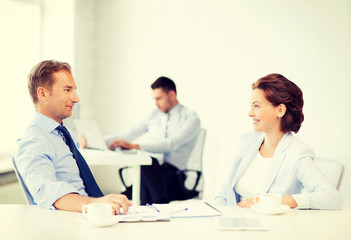 man and woman discussing something in office