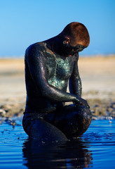 man applying black healing clay outdoors
