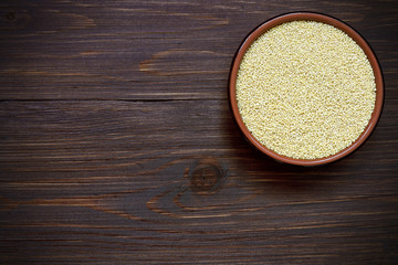 Organic uncooked millet in a bowl on a wooden table