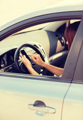 woman using phone while driving the car