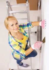smiling woman in gloves doing renovations at home