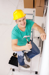 smiling man in helmet hammering nail in wall