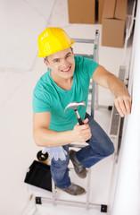 smiling man in helmet hammering nail in wall