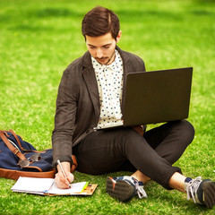 young fashion male student sitting on grass in park
