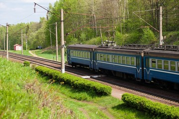 train rides on the rail on the background of green forest