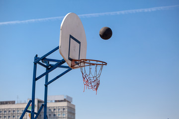 white basketball backboard and hoop on background of blue sky