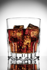 Faceted glass of cola with ice
