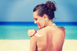 A woman is applying sunblock