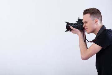 Young photographer on isolated white background