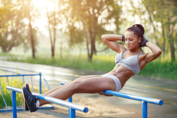 beautiful fitness woman doing sit-ups on bars sunny outdoor