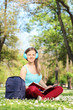 Young girl with headphones studying in park