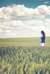 Toned retro style image of a girl in a wheat field
