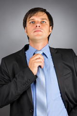 Portrait of a young businessman adjusting his neck tie getting r