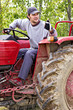 Young farmer driving his tractor and making ok sign