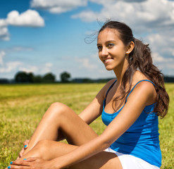 Tanned beautiful young woman in a field