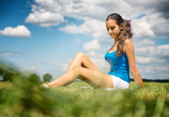 Beautiful girl relaxing in a green field