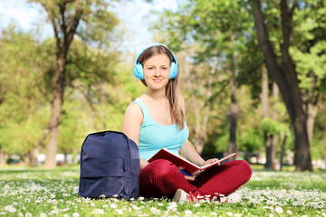 Girl studying in park and listening to a music