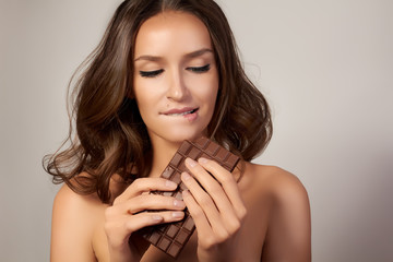 Beautiful girl with chocolate organic foods, feeling temptation