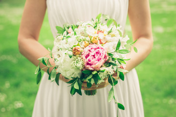 Beautiful bride outdoors holding wedding bouquet