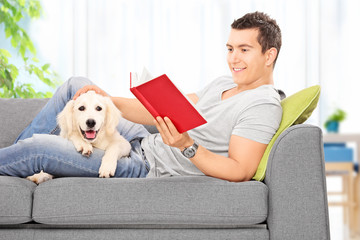 Man reading book and relaxing with a puppy at home