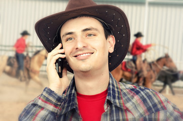 Young cowboy talking on smartphone