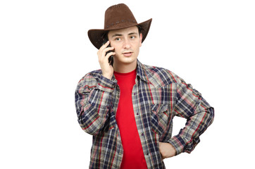 Young cowboy listening to someone on the smartphone