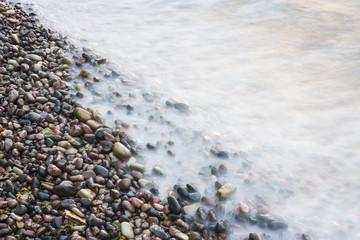 Sea waves on small rocks at seashore