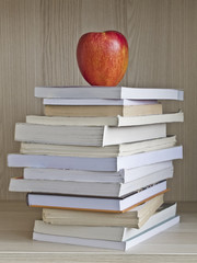 Books on shelf with apple