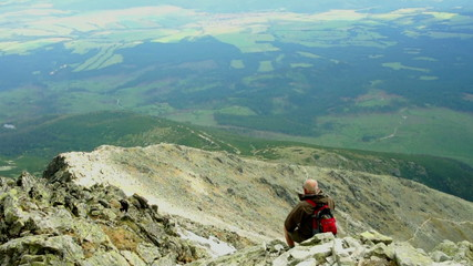 Man at the mountain peak looking at beautiful view