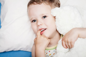 Cute child in bed with teddy bear