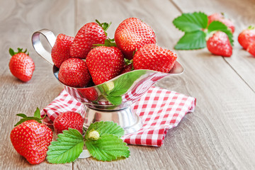 Bowl with ripe strawberries on wooden table
