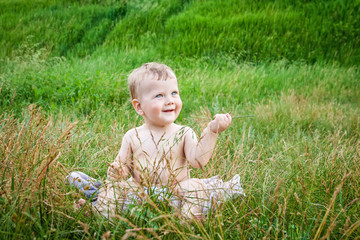 Cute boy playing in high grass on summer day
