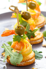 Canapes with shrimps, cheese and arugula.