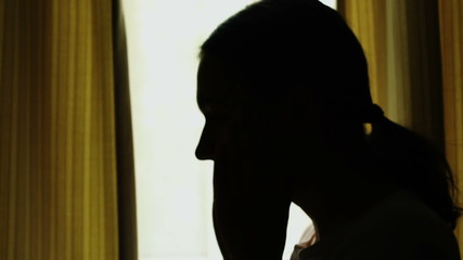 Silhouette of a young sad woman sitting near the window