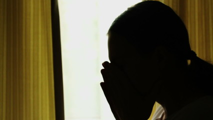 Silhouette of young woman with headache, slow motion
