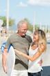 glückliches älteres paar mit surfbrett