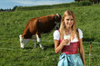 Bäurin vor einer Kuhweide mit einem Glas Milch in der Hand