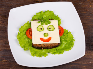 Face on bread, made from cheese, lettuce, tomato, cucumber