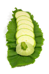 Sliced fresh light green zucchini on horseradish leaf isolated