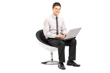 Man working on laptop seated in a modern chair