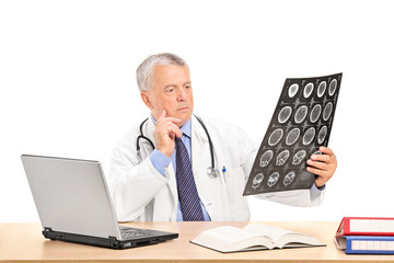 Doctor analyzing an x-ray seated at a table